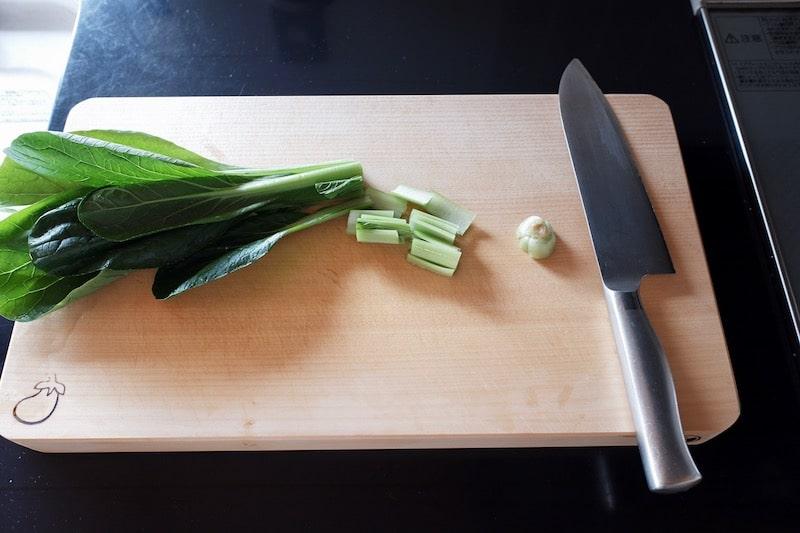イチョウのまな板の上に包丁と小松菜が乗っている様子