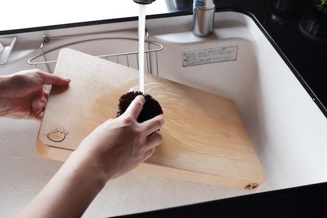 木のまな板をたわしで洗っている様子