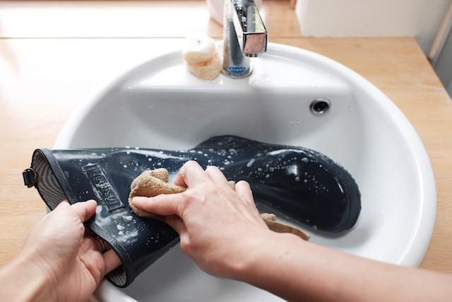 雑巾で長靴の汚れを拭き取っている様子