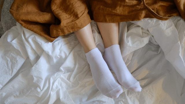 膝掛けをして靴下を履いている女性