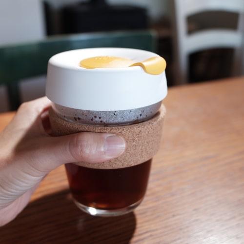 キープカップにコーヒーを入れて片手で持っている様子