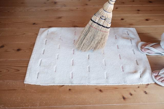 江戸箒でラグを掃いている様子