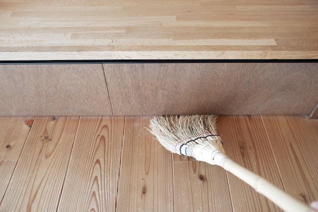 家具の下の隙間を掃く様子