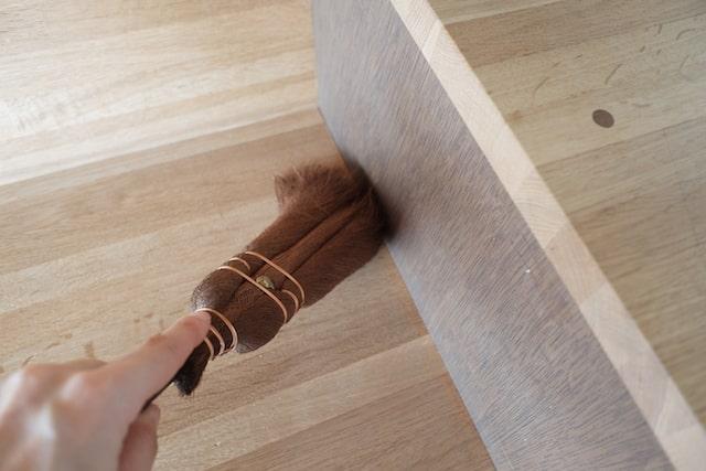 家具の角に溜まった埃を掃いている様子