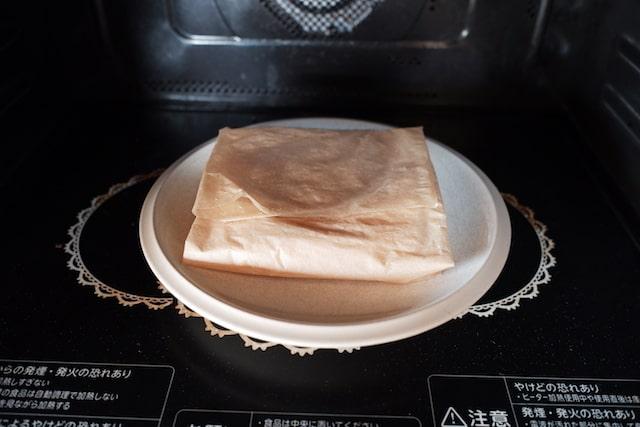 クッキングシートに包んだご飯をお皿に乗せて電子レンジで温める様子
