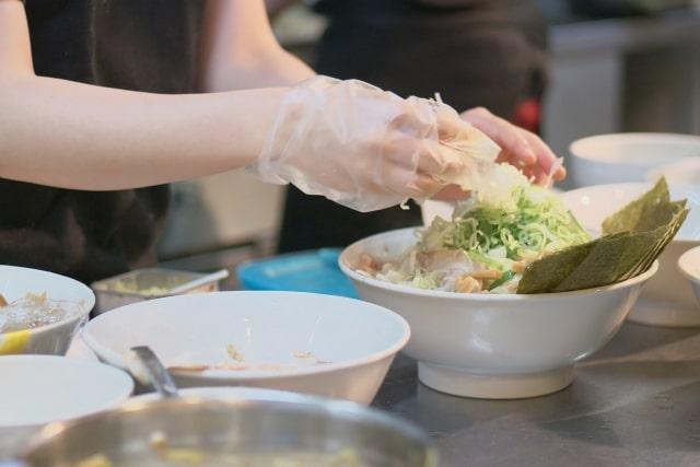 ポリエチレンの手袋をして料理をする女性