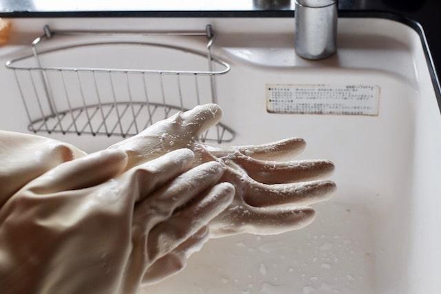 裏返ったゴム手袋をはめて石鹸で洗っている様子